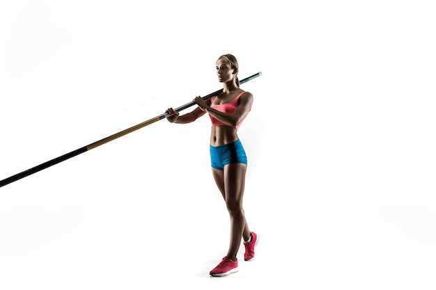 Power and beauty and purity. professional female pole vaulter training on white wall. fit and slim female model practicing. concept of sport,