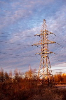 Электростанция. опора высоковольтной передачи электроэнергии. высоковольтная линия электропередачи на закате. высоковольтная мощность и красочное небо. передающие башни