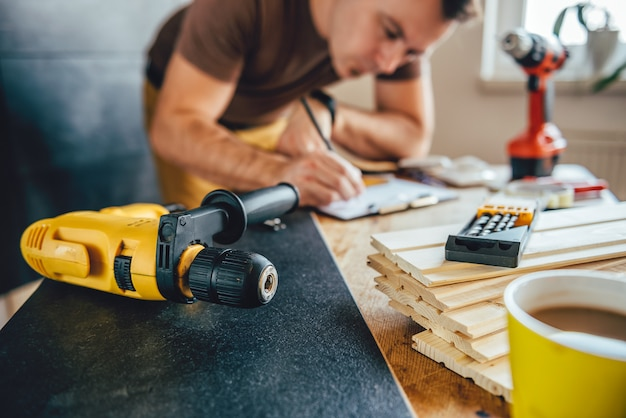 Power drill and man making draft plan in the