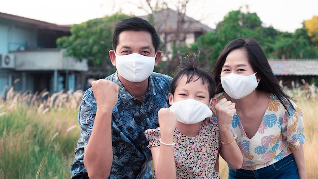 Power of family with father mother and daughter wearing medical face mask for protect 2019 - ncov , covid 19 or corona virus.stay at home concept