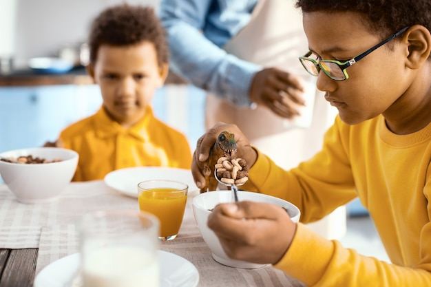 Power of imagination. pleasant pre-teen boy holding a spoonful of cereals and feeding them to his toy dinosaur during breakfast