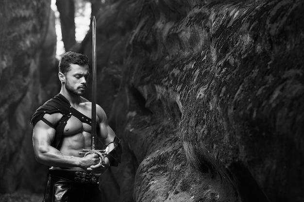 평화의 힘. 숲의 바위 근처에 칼을 들고 서 있는 차분한 사려 깊은 전사의 흑백 샷. 근육질의 몸통이 copyspace 포즈를 취하는 강한 젊은이