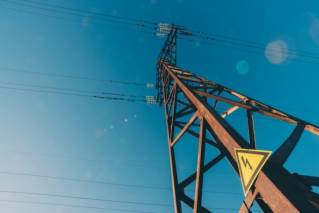 Power lines on background of blue sky close-up. electric hub on pole. electricity equipment with copy space. wires of high voltage in sky. electricity industry. tower with lightning warning sign.