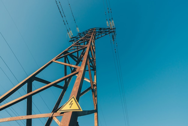 Power lines on background of blue sky close-up. electric hub on pole. electricity equipment with copyspace. wires of high voltage in sky. electricity industry. tower with lightning warning sign.