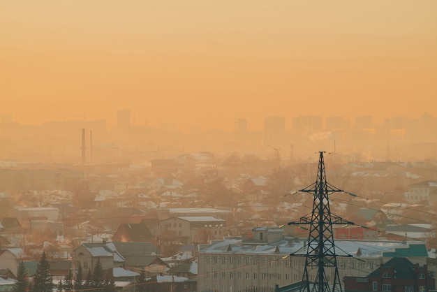 Power lines in city on dawn. silhouettes of urban buildings among smog on sunrise. cables of high voltage on warm orange yellow sky. power industry at sunset. city power supply. mist urban background.