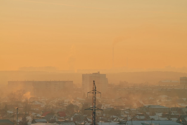 Power lines in city on dawn. silhouettes of urban buildings among smog on sunrise. cables of high voltage on warm orange yellow sky. power industry at sunset. city power supply.