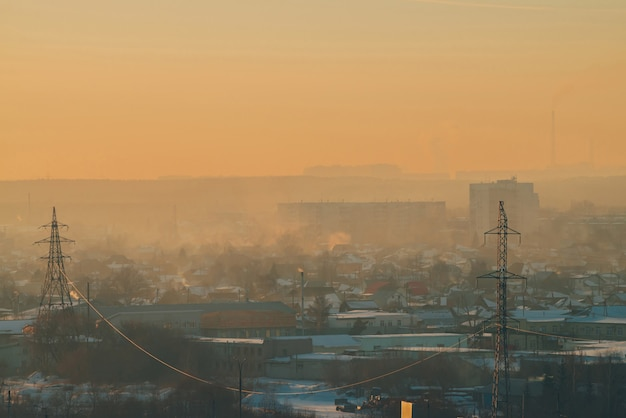 Power lines in city on dawn. silhouettes of urban buildings among smog on sunrise. cables of high voltage on warm orange yellow sky.