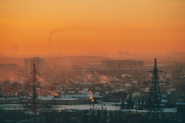 Power lines in city on dawn. silhouettes of urban buildings among smog on sunrise.