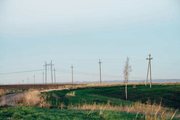 Power lines in field under blue sky