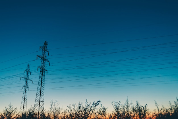 Power lines in field on sunrise background