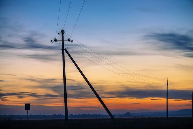 Power lines in field on sunrise