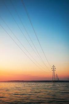 원자력 발전소에서 반대편 해안까지의 전력선. 일몰과 호수가 있는 아름다운 풍경.