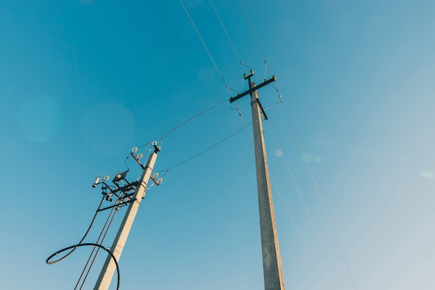 Линии электропередач на фоне голубого неба крупным планом