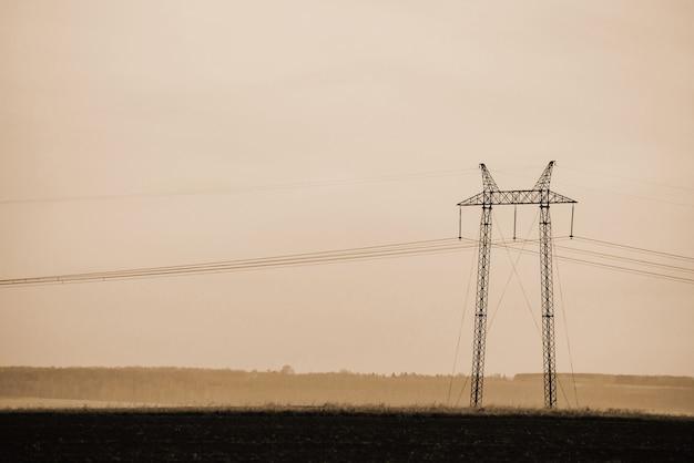 空のセピア色の背景に電力線をクローズアップ