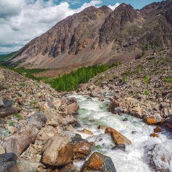 Мощная горная река стекает с ледника. красивый альпийский пейзаж с лазурной водой в быстрой реке. сила величественной природы высокогорья.
