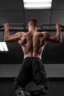 Power muscular bodybuilder guy doing pullups in gym fitness man pumping up lats muscles