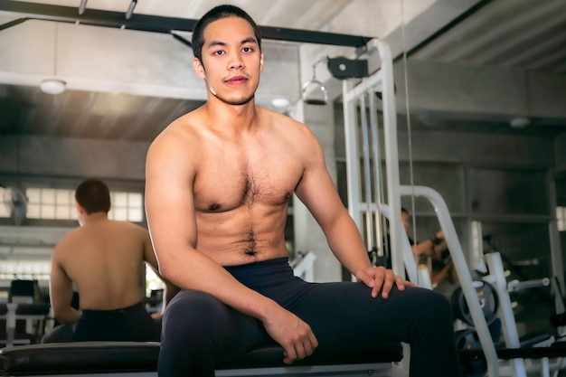 Power muscular handsome asian man strong and healthy smiling in gym after workout.
