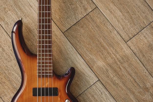 악기의 힘. 나무 바닥에 누워 있는 갈색 일렉트릭 기타의 최고 전망. 음악 장비. 악기. 음악 개념