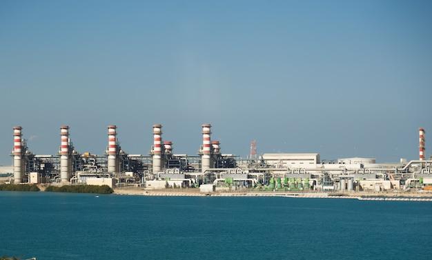 Электростанция у пруда. пейзаж с большими трубами.
