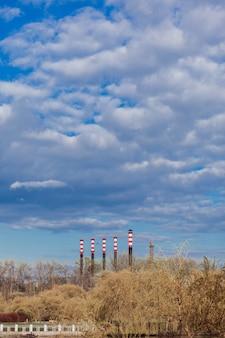 Высокие трубы электростанции, загрязняющие атмосферу на закате.