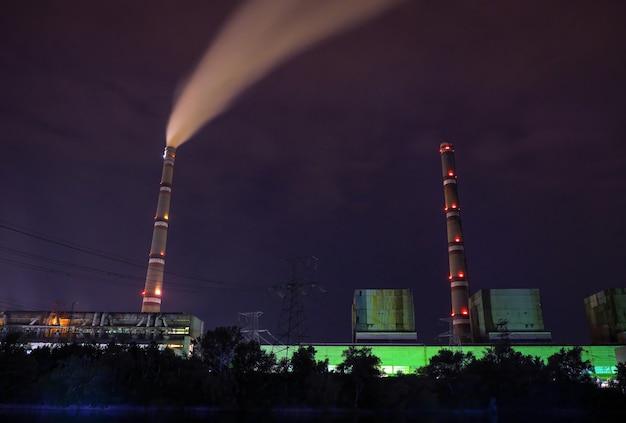 Электростанция с трубами в ночное время. темное фото