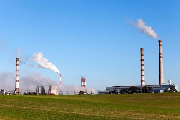 Электростанция с дымовой трубой во время работы. издали крупным планом. голубое небо в осенний сезон
