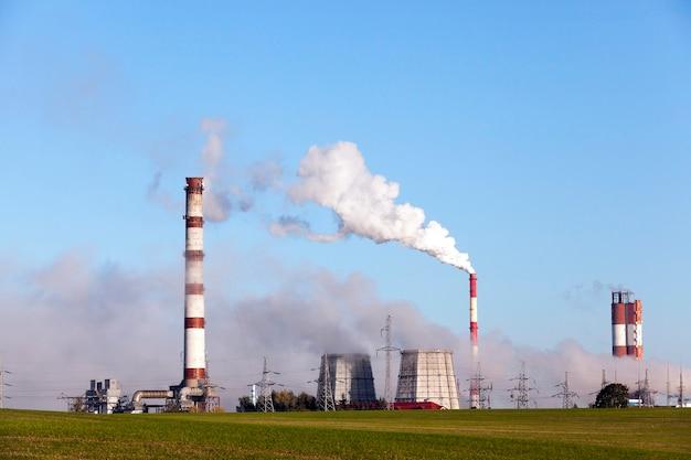 작동 중 연기 파이프가있는 발전소. 거리 클로즈업에서 사진. 가을 시즌에 푸른 하늘