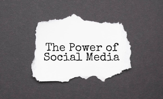 The power of social media sign on the torn paper on the black surface