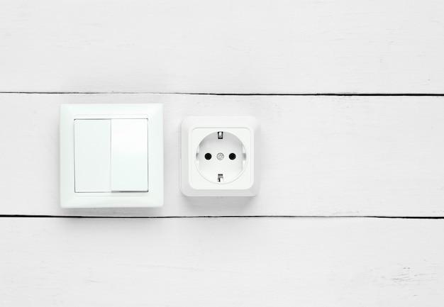 Розетка и выключатель на белой деревянной стене
