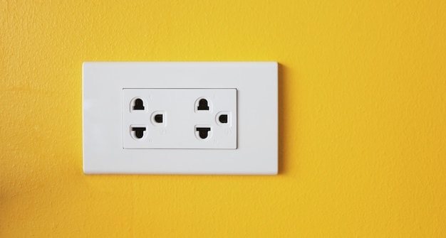 The power sockets on the walls are painted in bright yellow.