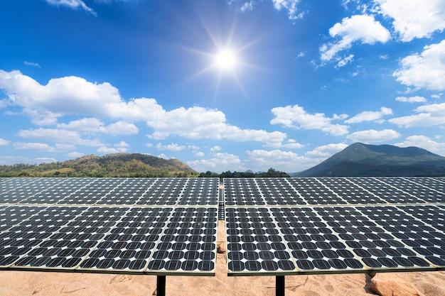 Панели солнечных батарей на ландшафте песчаный пляж и озеро, природа, лес, вид на горы, голубое небо, белое облако, концепция альтернативных источников энергии и чистая энергия.