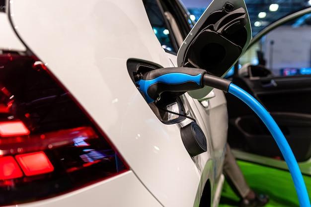 電気自動車充電用電源。電気自動車充電ステーション。充電中の電気自動車に接続されている電源の拡大図。
