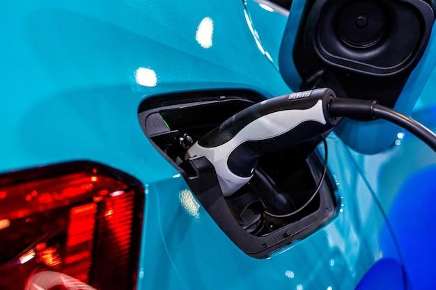 전기 자동차 충전 용 전원 공급 장치, 전기 자동차 충전소, 충전중인 전기 자동차에 연결된 전원 공급 장치의 클로즈업 프리미엄 사진