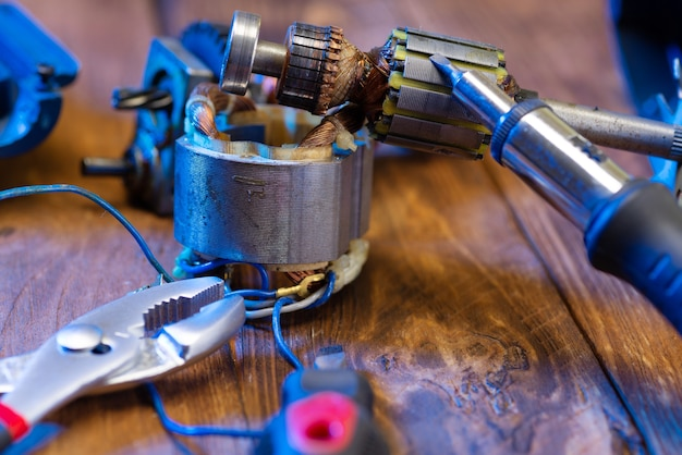 Power tool repair. details of an electrical appliance and tools for repair on a wooden table in a repair shop. a foreman repairs a power tool using a soldering iron and pliers