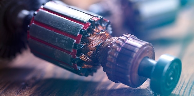 Ремонт электроинструмента. детали электроприбора и инструментов для ремонта на деревянном столе в ремонтной мастерской.