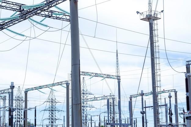 パワータワー。高圧線と送電鉄塔。都市変電所、クローズアップ、高電圧線を備えた変圧器。接続された高電線に設置された高圧送電線
