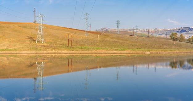 Башни лэп в горной долине у озера
