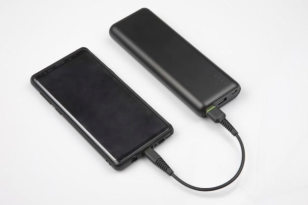 Powerbank заряжает аккумулятор смартфона на белом фоне. цифровые технологии и устройства