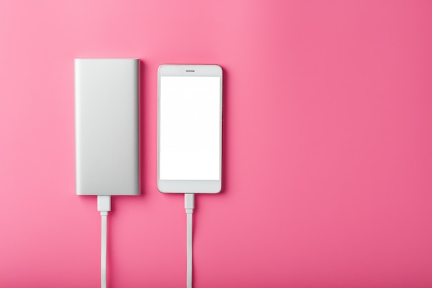 Powerbank는 분홍색 배경에 스마트 폰을 충전합니다. 가제트를위한 범용 외부 배터리 여유 공간과 최소한의 구성.