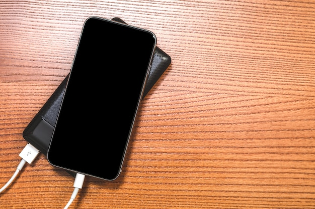 Powerbank charges smartphone isolated on wood