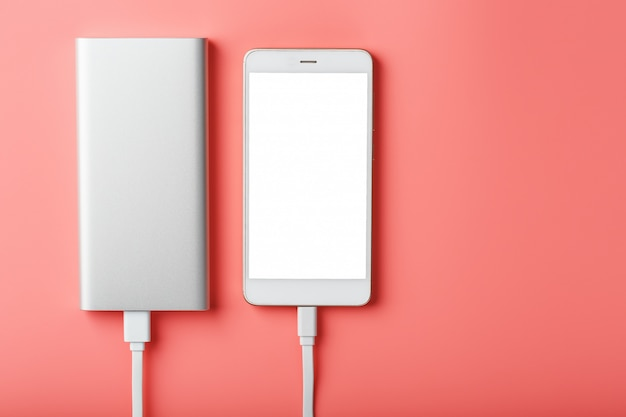 Powerbank charges a smartphone on a pink background. universal external battery for gadgets free space and minimalistic composition.