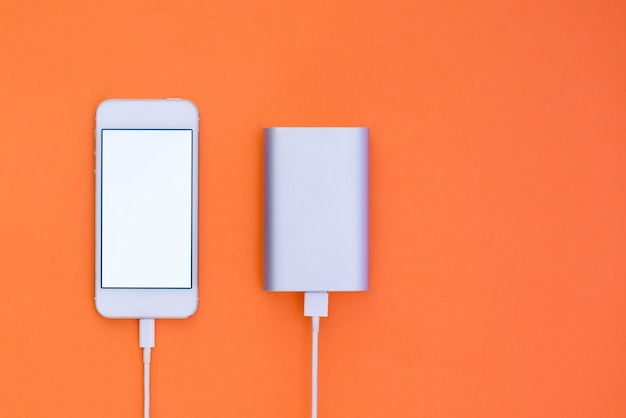 Powerbank and phone on orange background. flat lay phone layout that charges with powerbank