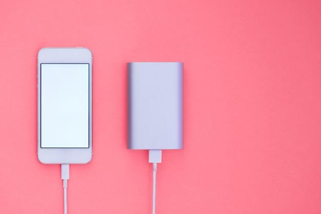 Powerbank и телефон на розовом фоне. плоское расположение телефона, которое заряжается с powerbank