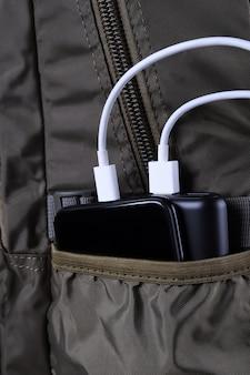 電話の充電、powerbankはスマートフォン、携帯電話をエネルギーバンクで充電します。バックパックバッグのパワーバンクの被写界深度