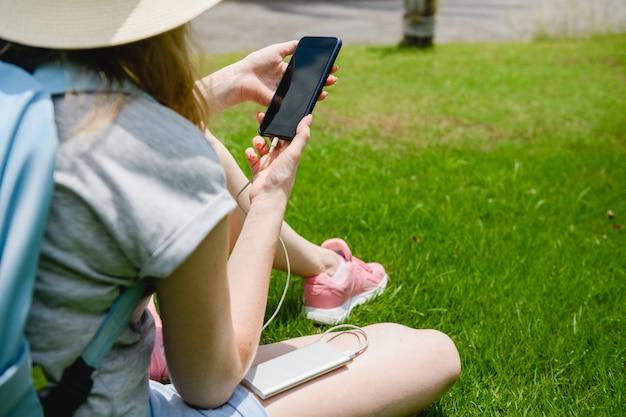 Девушка заряжает телефон с powerbank на траве