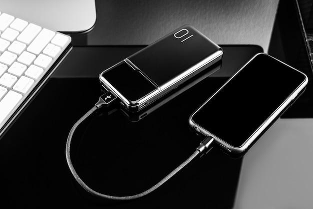 Powerbank、黒い表面に分離されたスマートフォンを充電