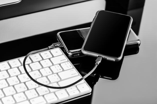 Powerbank заряжает смартфон, изолированный на черной поверхности