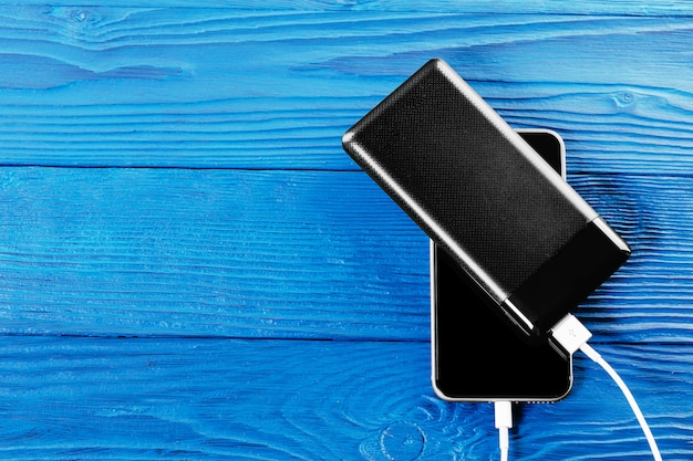 Powerbank、青い木製の表面に分離されたスマートフォンを充電