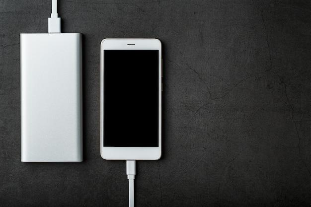 Белый powerbank заряжает смартфон. универсальный внешний аккумулятор для гаджетов. свободное пространство.
