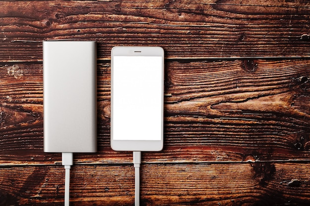 Powerbank заряжает смартфон на деревянном фоне. универсальный внешний аккумулятор для гаджетов. свободное пространство и минималистичная композиция.